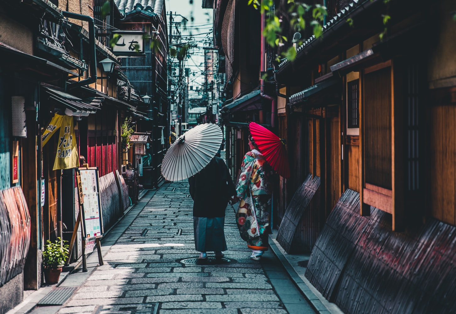 Geishas with parasols walking down Japanese laneway