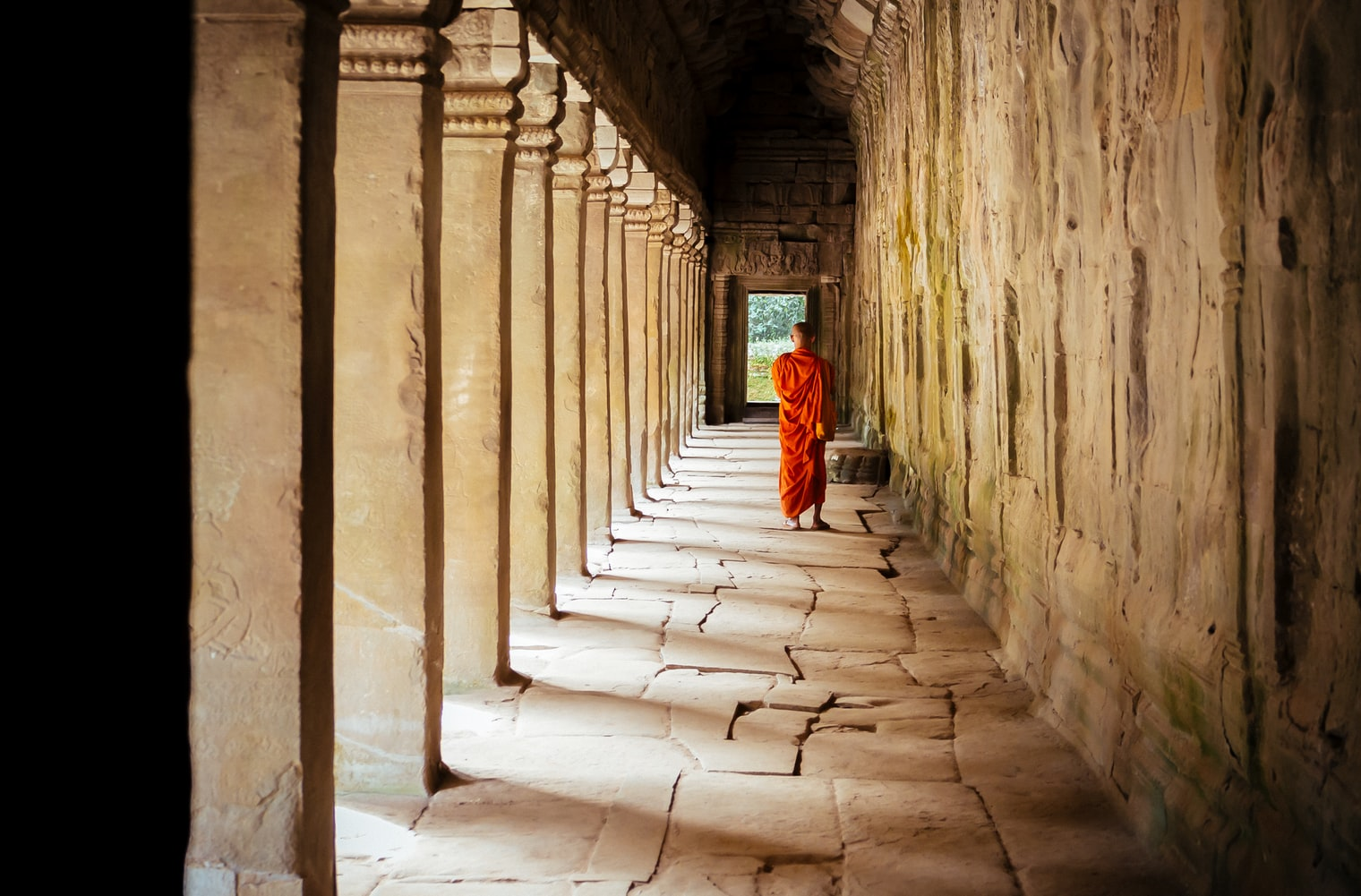 Buddhist monk walking down temple colonnade