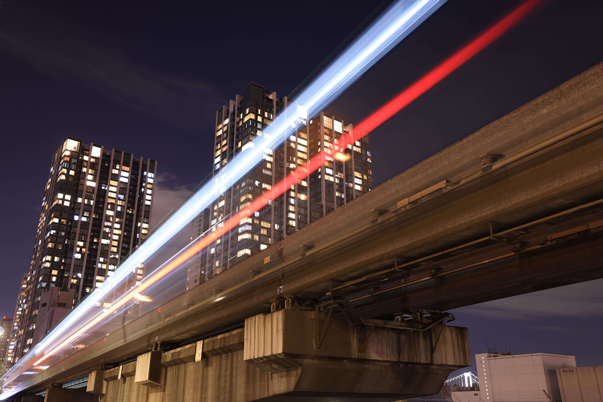 Light trails above an elevated concrete bridge with lit-up high rises in the background, photographed with the Canon EOS R5