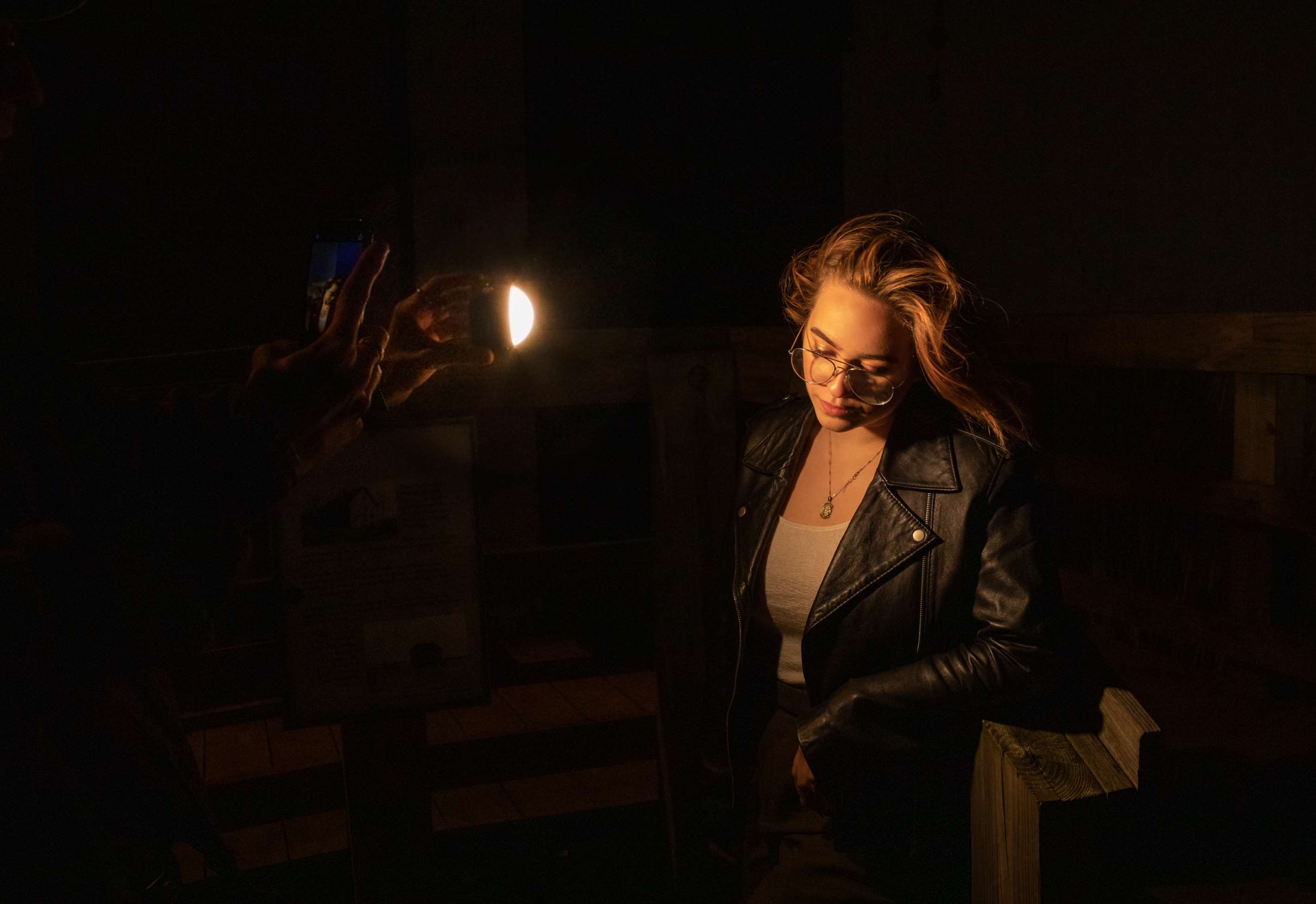 Profoto C1 professional smartphone light being used to photograph female model in glasses and leather jacket