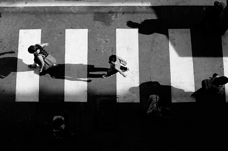 black and white photo of people walking on a pedestrian lane