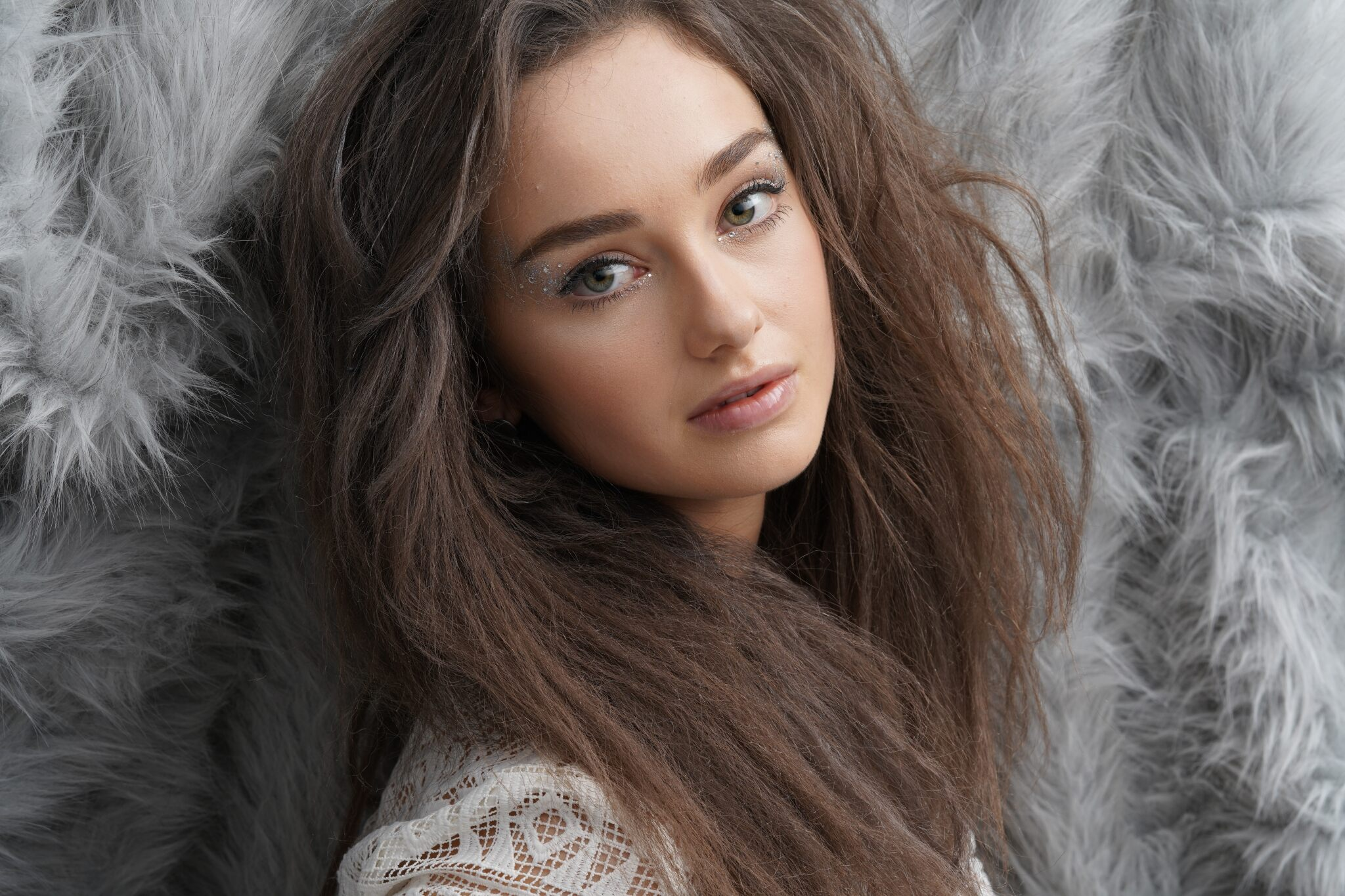 Fashion model with teased brown hair posed against a grey shagpile backdrop, photographed with the Sony a7R Mark IV camera