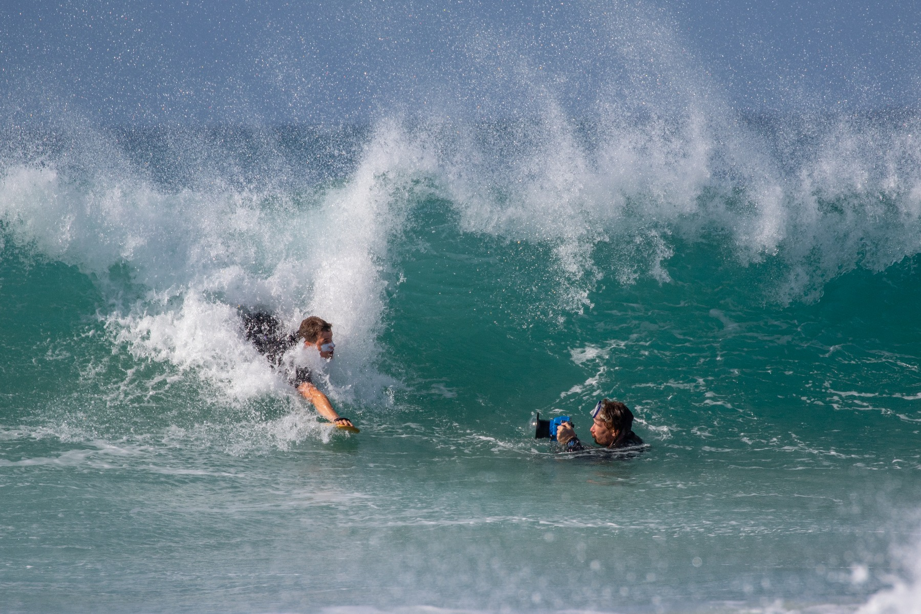 man taking a picture of a person surfing