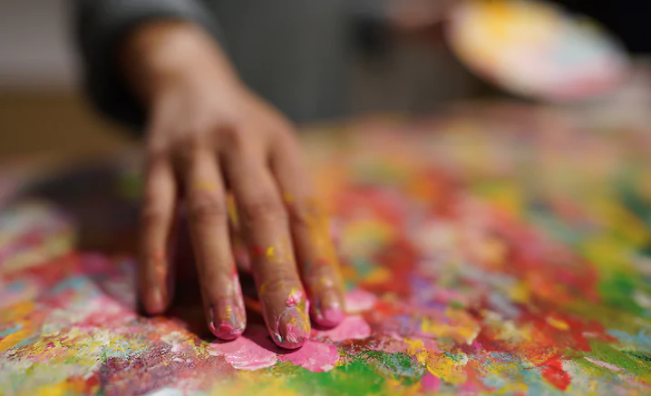 Close-up of artist's hand fingerpainting in bright colours, photographed with the Sony 24mm 1.4 GM lens