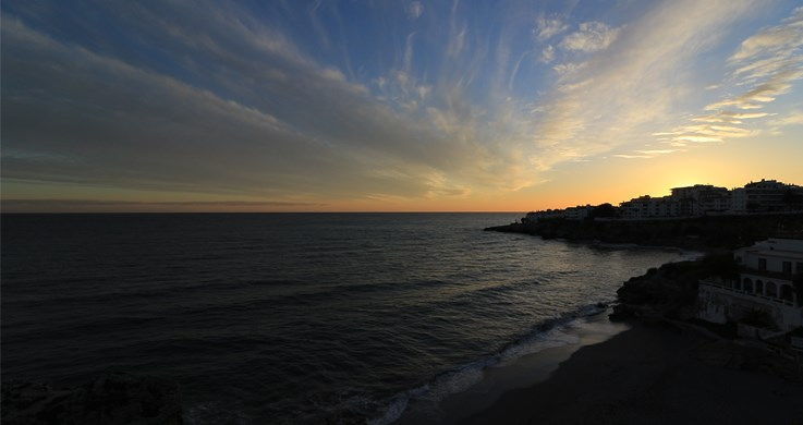 Cloudy sunset over the ocean and a coastal town, photographed with the Canon 10-18mm wide angle lens