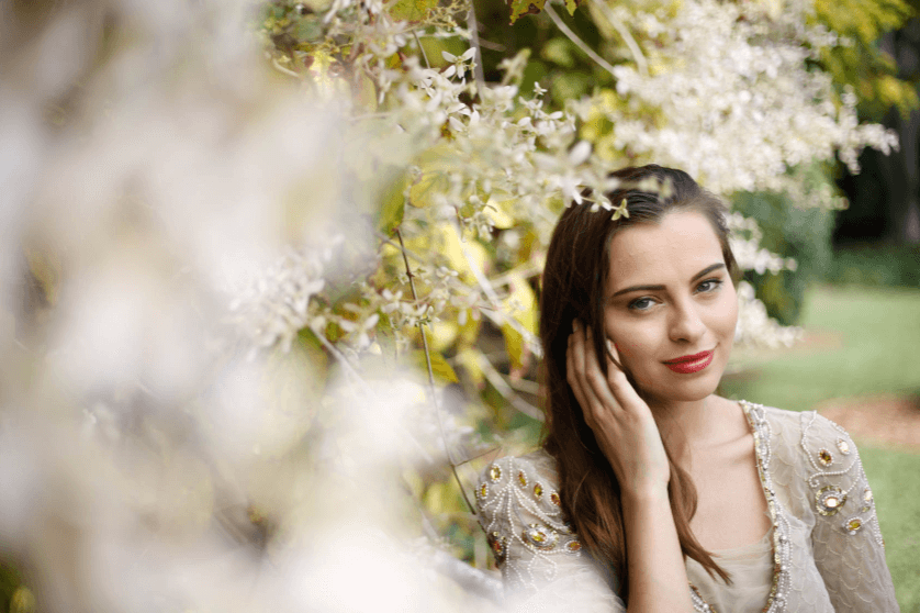 Elegantly dressed young woman with white flowers in the foreground and background, taken with the Canon 50mm 1.8 STM lens