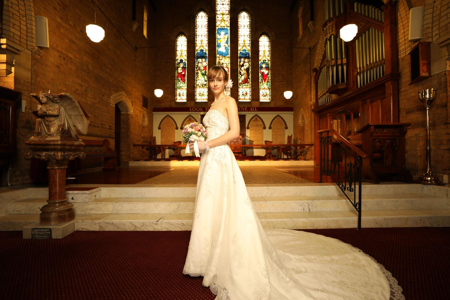Bride in a white lace dress, standing inside a church with stained-glass windows, shot with Canon EF 16-35mm f/2.8L III Lens