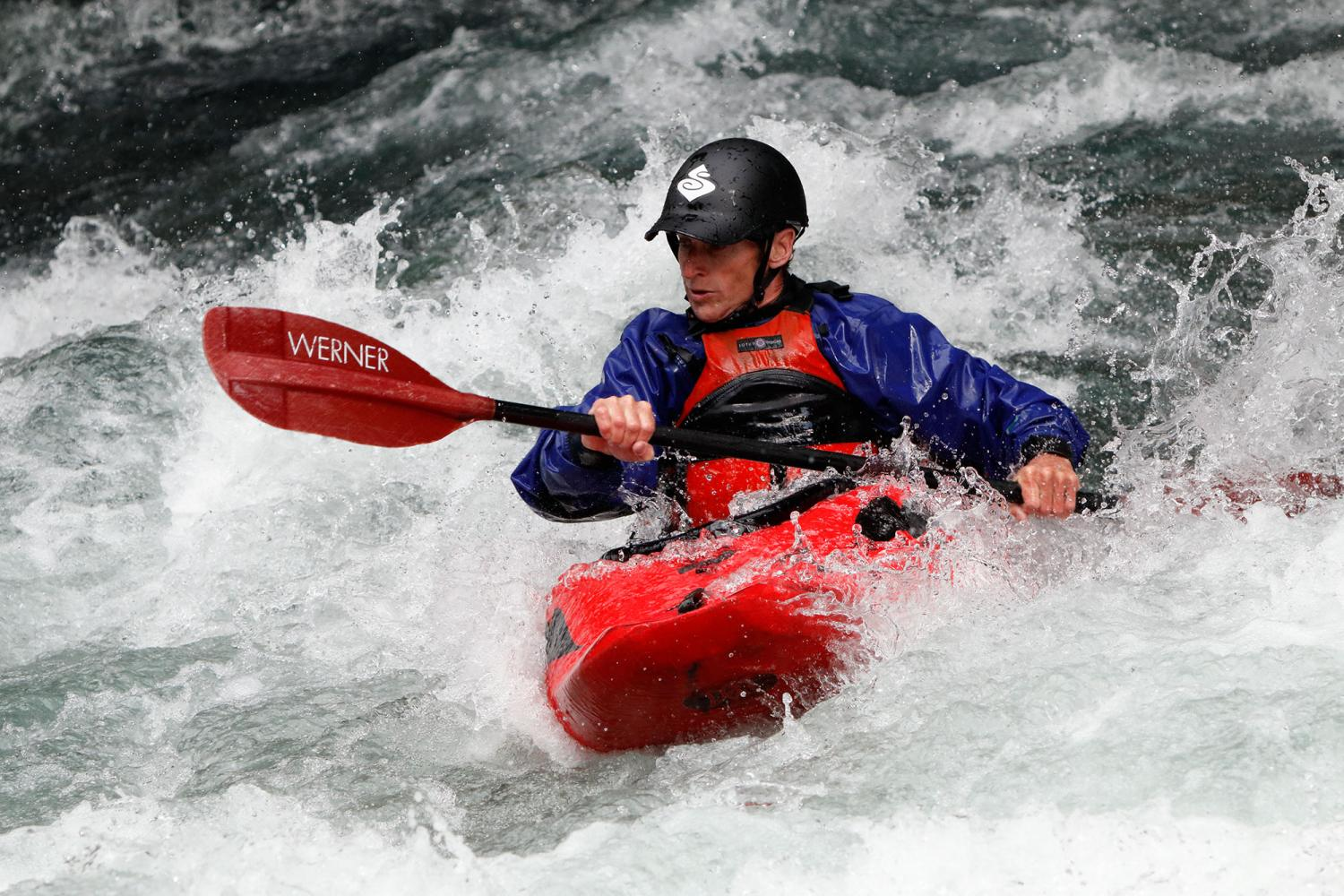 Man in red kayak paddling through white water currents, photographed with the Canon EF 70-300mm f/4-5.6 IS II USM lens