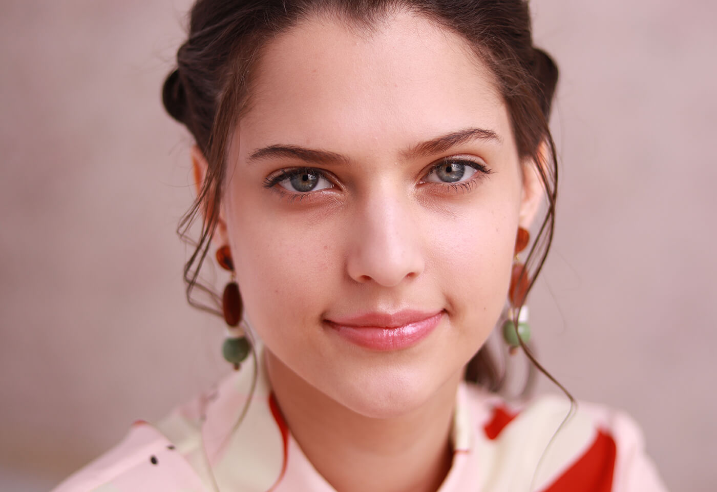 Young woman with brown hair and dangling earrings smiling in front of a pale backdrop, photographed with the Canon EOS M50