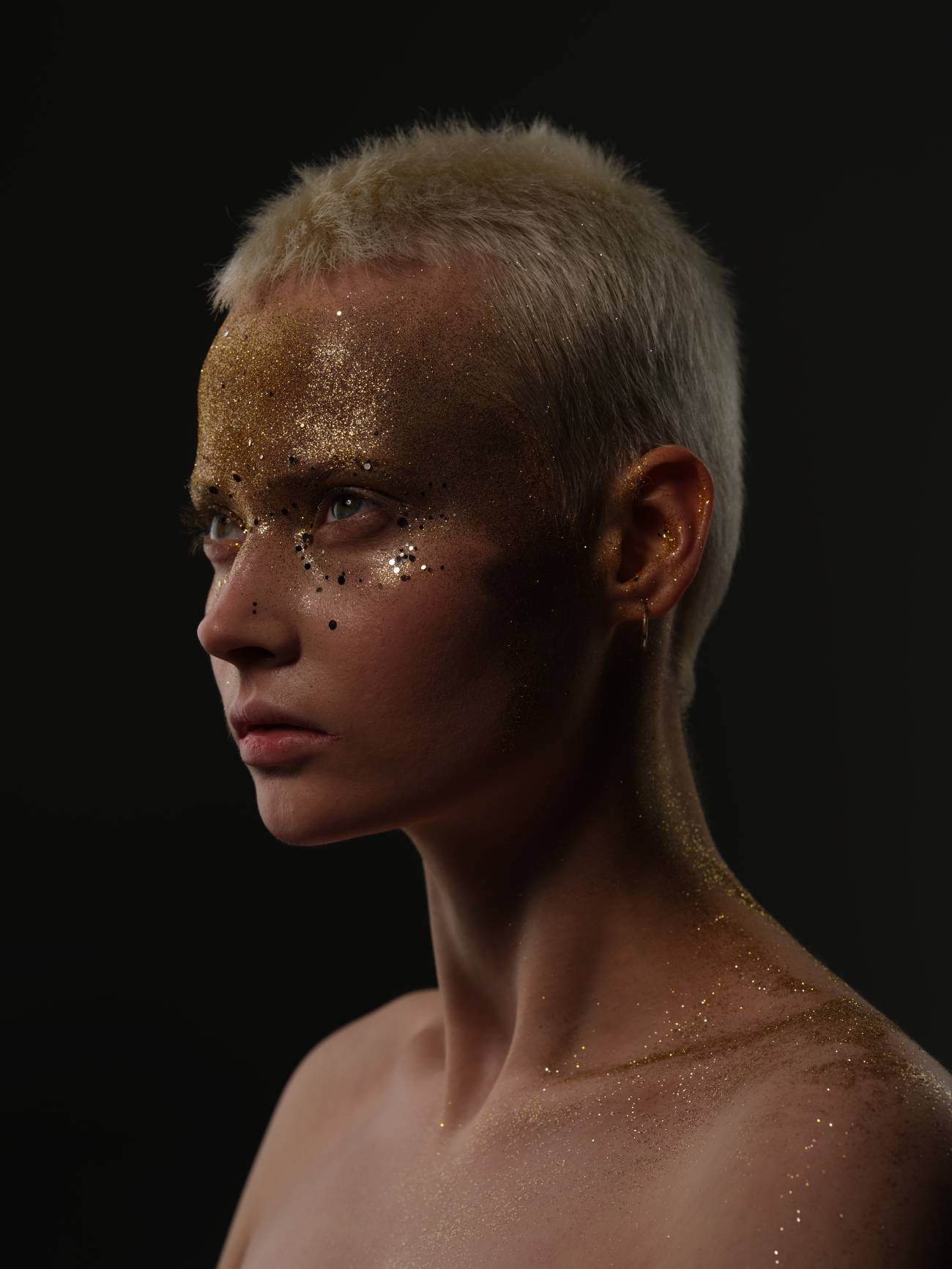 Model with short blonde hair looking upwards, her forehead covered with gold glitter – photographed with the Fujifilm GFX100