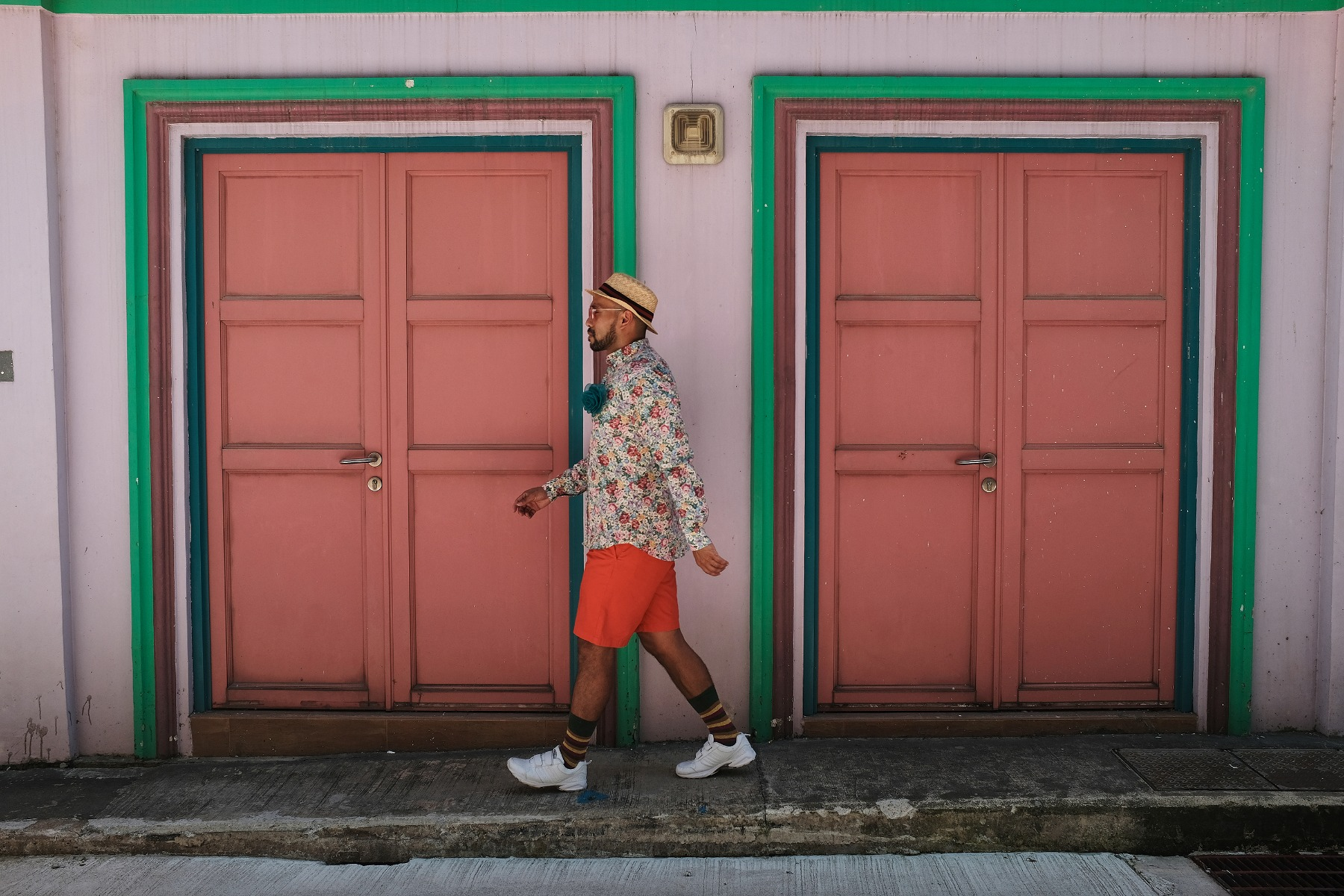 Bearded man in a hat, floral shirt & orange shorts walking past twin orange double doors, photographed with the Fujifilm X100F