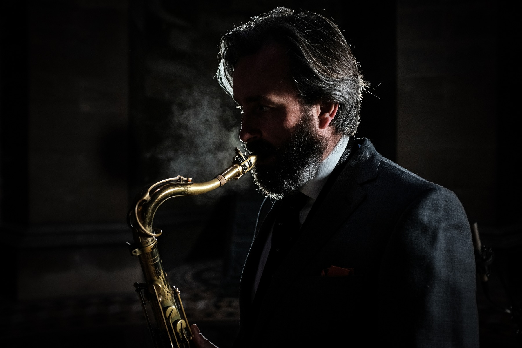 Bearded man in a suit jacket playing saxophone, his face partly obscured by shadow – photographed with the Fujifilm X100F