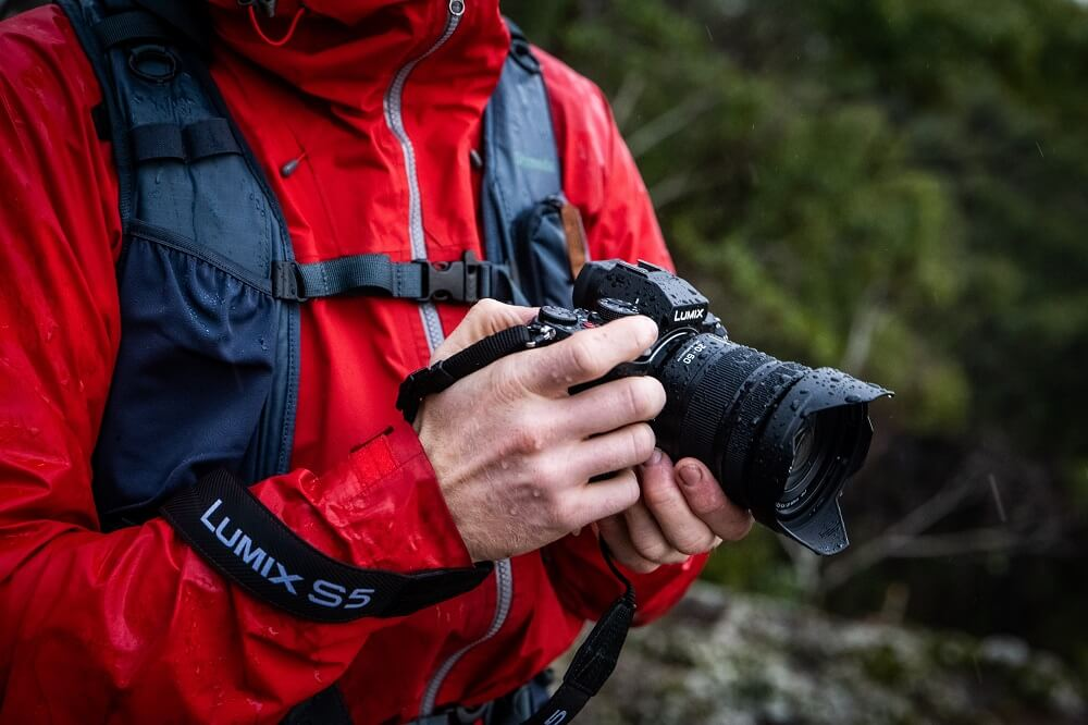 Man in a wet red windbreaker holding a Panasonic Lumix S5