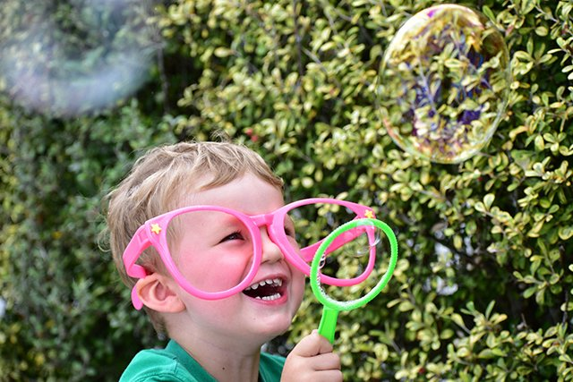 Young child in giant pink glasses laughing while blowing bubbles, photographed with the NIKKOR 70-300mm f/4.5-6.3 G ED VR lens