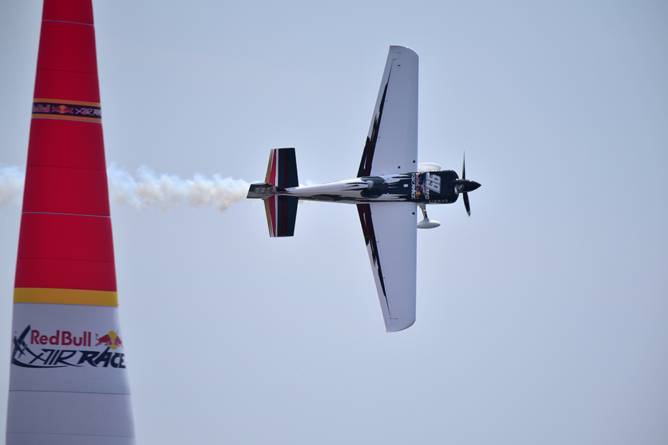 Plane flying on its side around an obstacle at the Red Bull Air Race, photographed with the