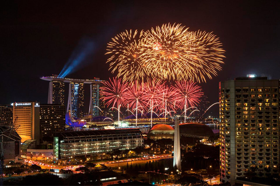 Fireworks beside Marina Bay Sands, above the city lights of Singapore, photographed with the Nikon 28-300mm f/3.5-5.6G ED VR