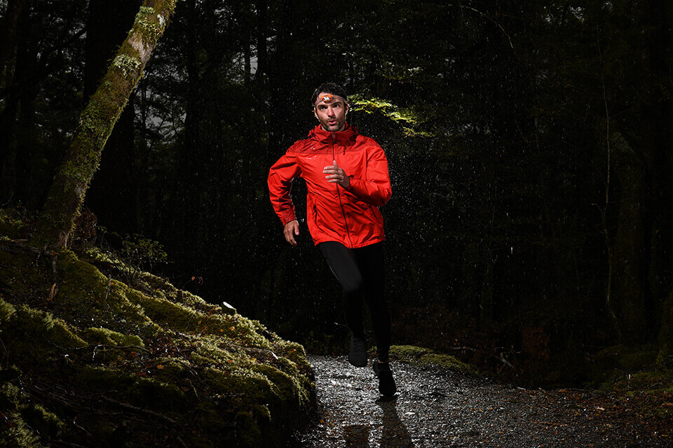 Man, wearing an orange jacket, jogging through a forest at night – photographed with the Nikon D7500 DSLR camera