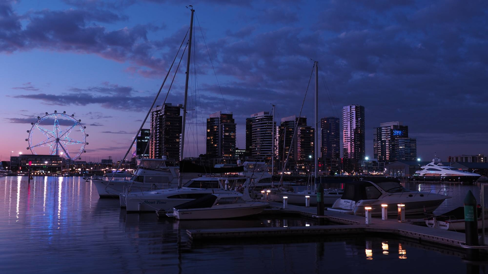 Marina at dusk, with high rises and a Ferris wheel lit up in the background, photographed with the Olympus OM-D E-M10 Mark II