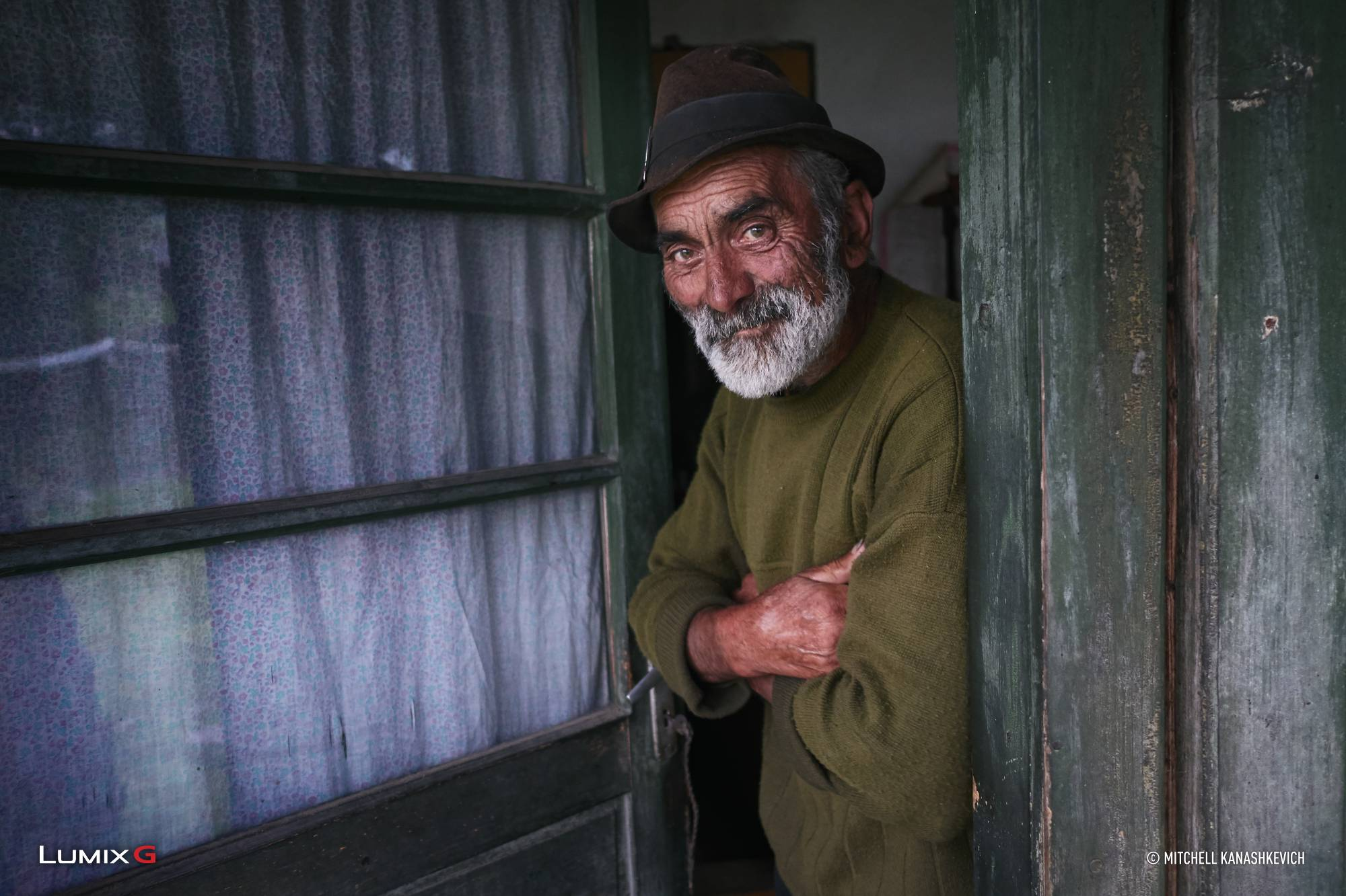 Grey-bearded man in a brown hat smiling in a rustic green doorway, photographed with the Panasonic LUMIX G85 camera