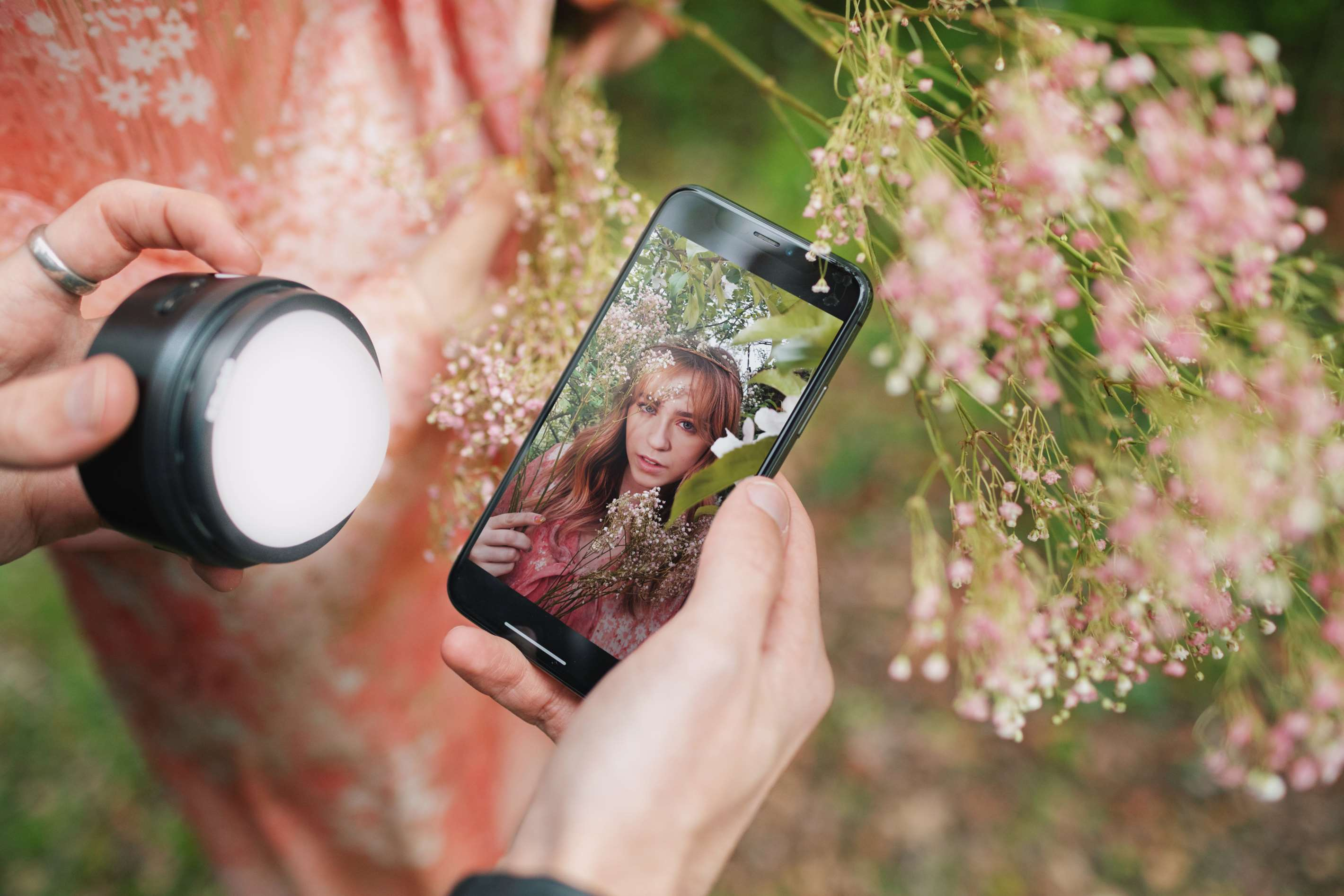 Hands holding Profoto C1 light & smartphone displaying photo of model with flowers, with same model & flowers in background