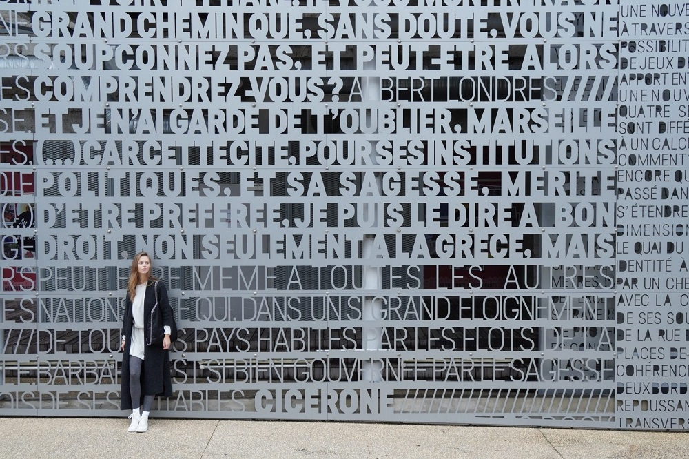 Young woman in long dark coat posing in front of a wall displaying French words, photographed with the Sony Alpha a6400