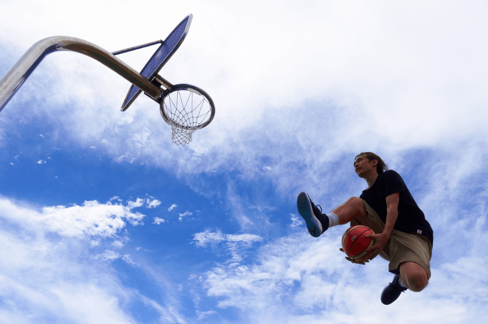 Basketball player aiming for the net, both photographed against a cloudy blue sky using the Sony RX100 Mark V compact camera