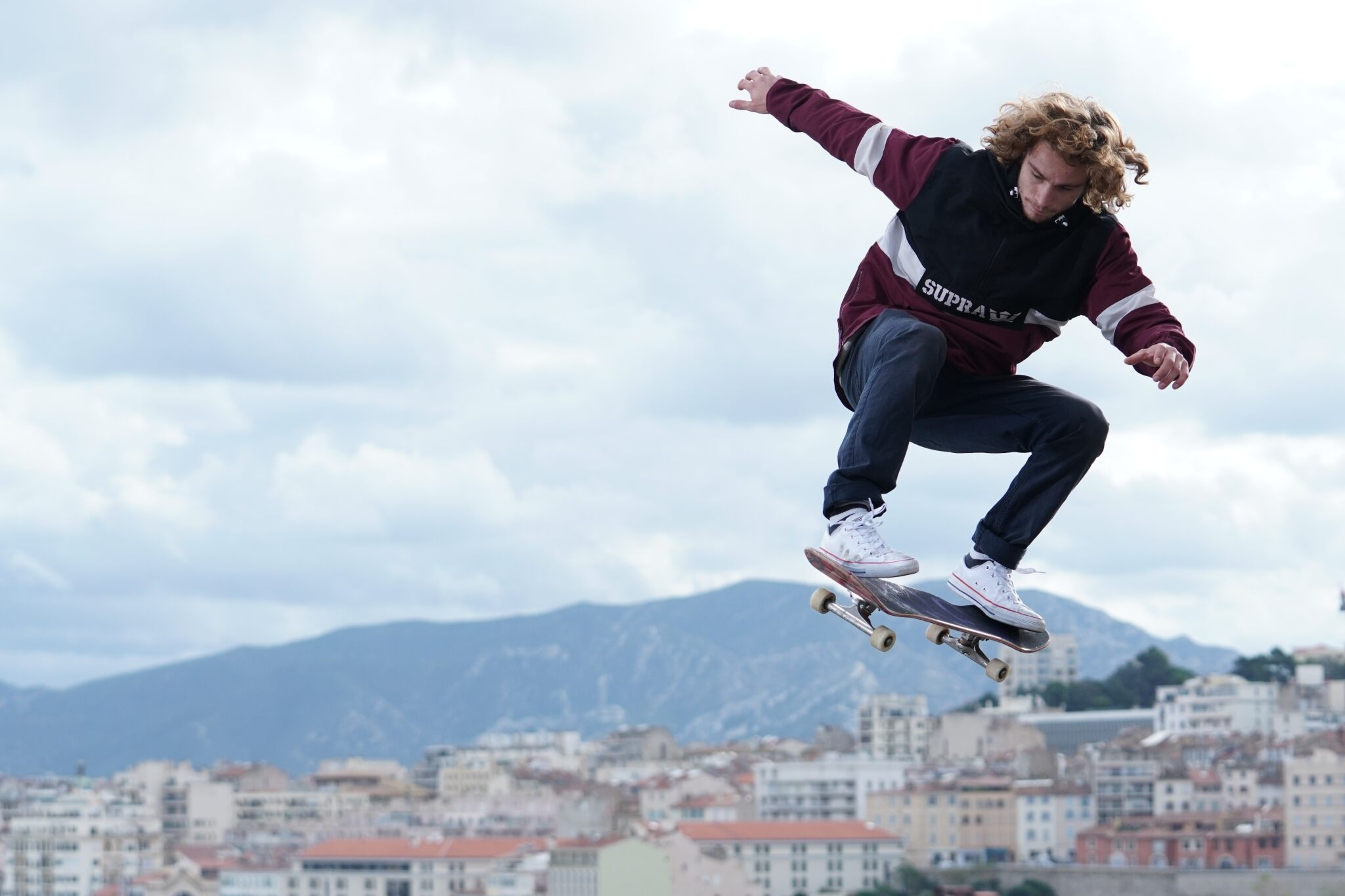 Young man skateboarding mid-air against a backdrop of buildings & mountains, shot with the Sony FE 70-200mm f/2.8 GM OSS lens