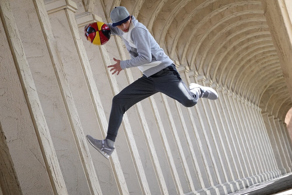 Young man suspended midair, basketball in hand, against a backdrop of colonnades, photographed with the Sony RX100 VI