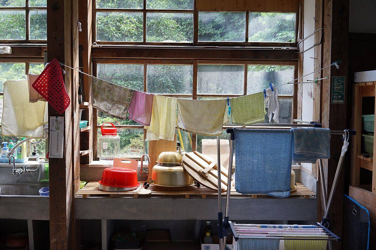 Cloths hung up to dry over a sink stacked with dishes in front of a sash window, shot with the Sony 35mm 2.8 ZEISS lens