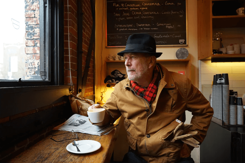 Man in jacket and hat holding a cup of coffee while seated inside a cafe, photographed with the Sony 24 to 70mm f4 Zeiss lens