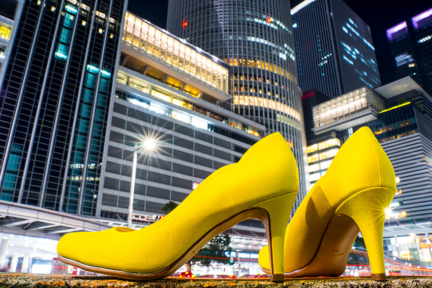 Bright yellow high heels in foreground dwarfing brightly lit modern buildings in background, shot with Tamron 28-75mm f/2.8