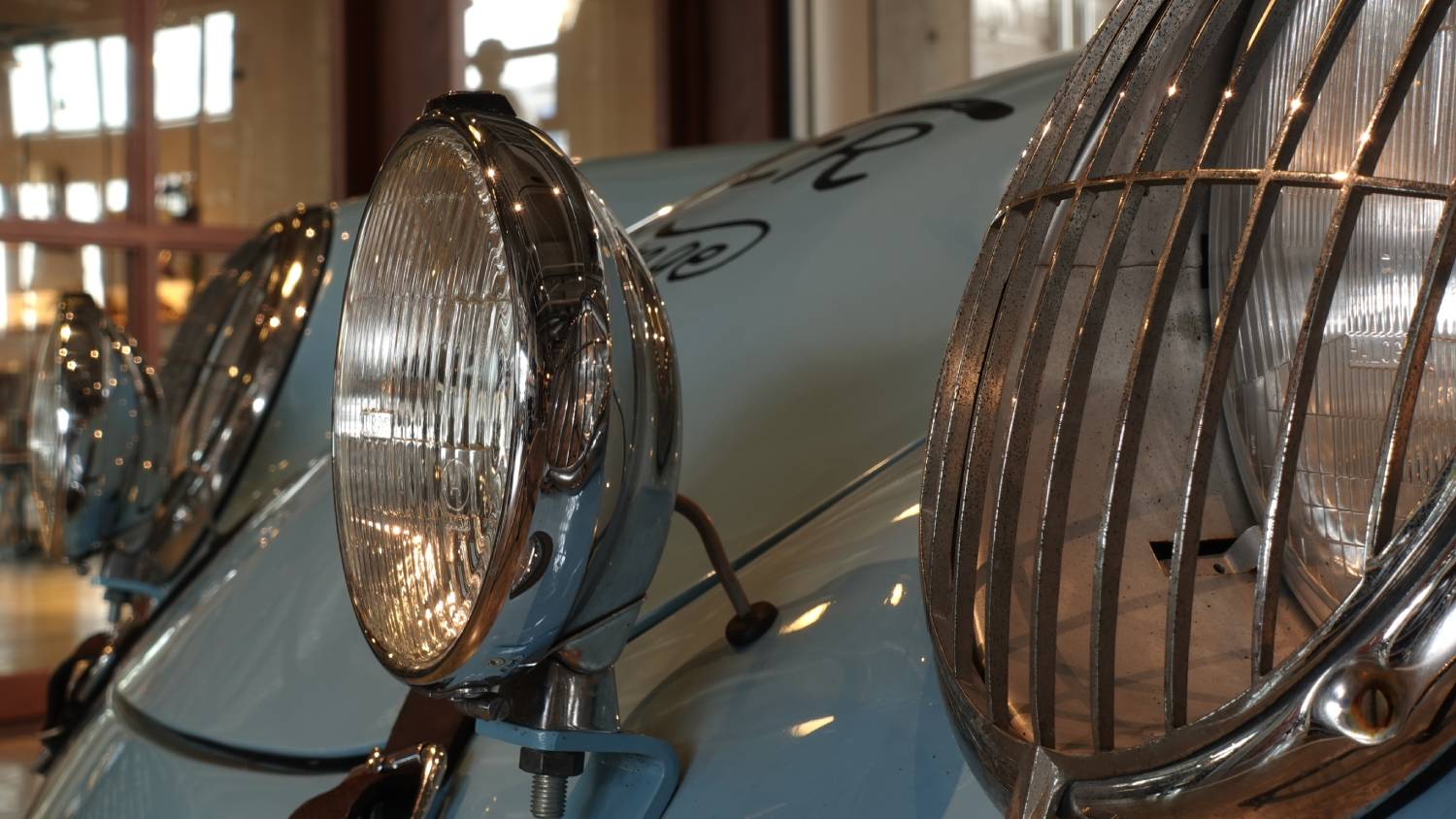 Close-up of headlights on a shiny, light blue vintage car, photographed with the Sony ZV-1 digital camera