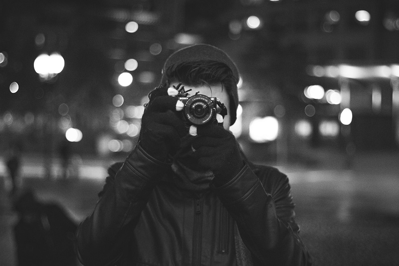 black and white photo of a man taking pictures on the street