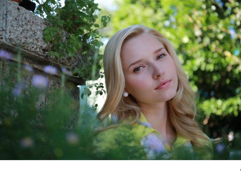 Young blonde-haired woman beside a pillar surrounded by greenery, photographed with the Canon EF 24-70mm f/4L IS USM Lens