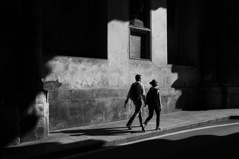 black and white photo of two people walking on the street