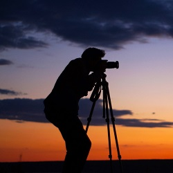 man taking pictures with a tripod during a sunset
