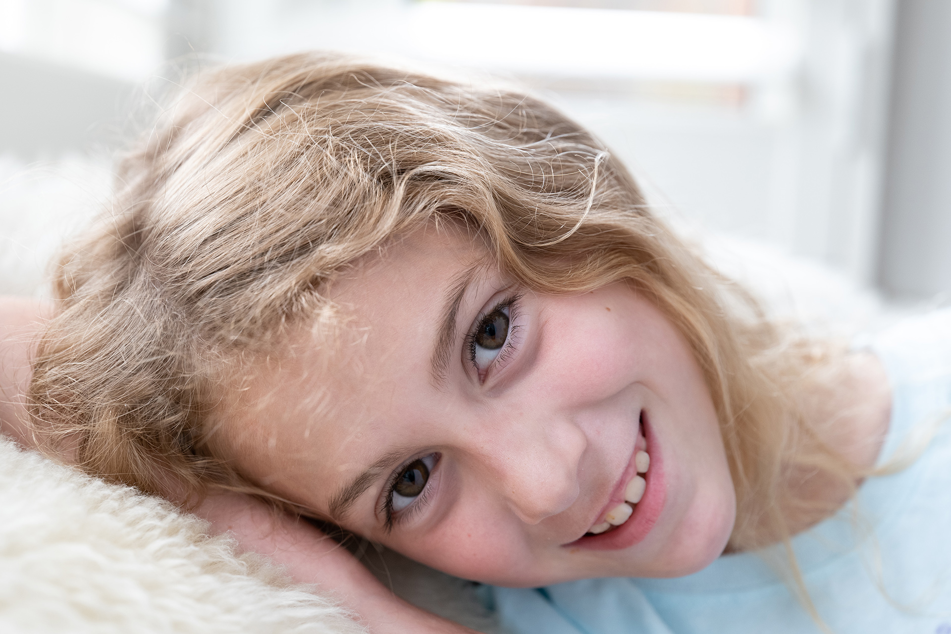 High key portrait of girl with blonde hair resting against shaggy white blanket, photographed using Panasonic Lumix S PRO 24-70mm f2.8 lens